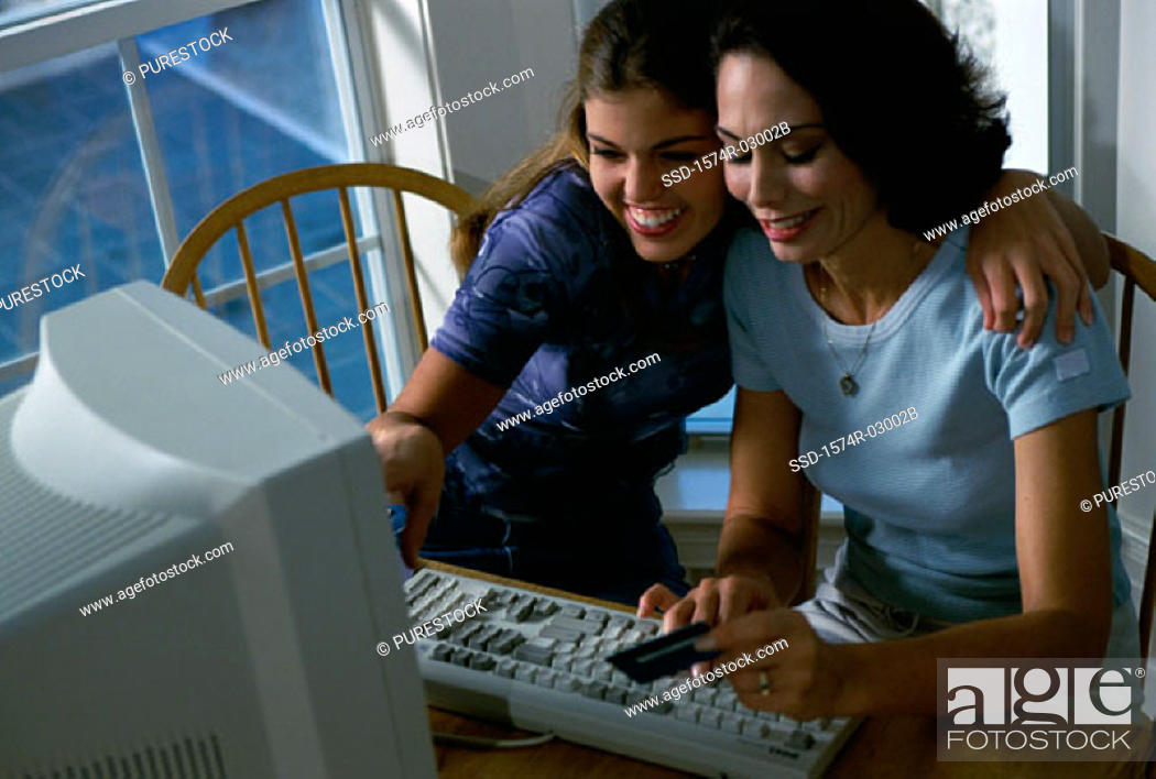 Stock Photo: Mother and her daughter sitting in front of a computer.