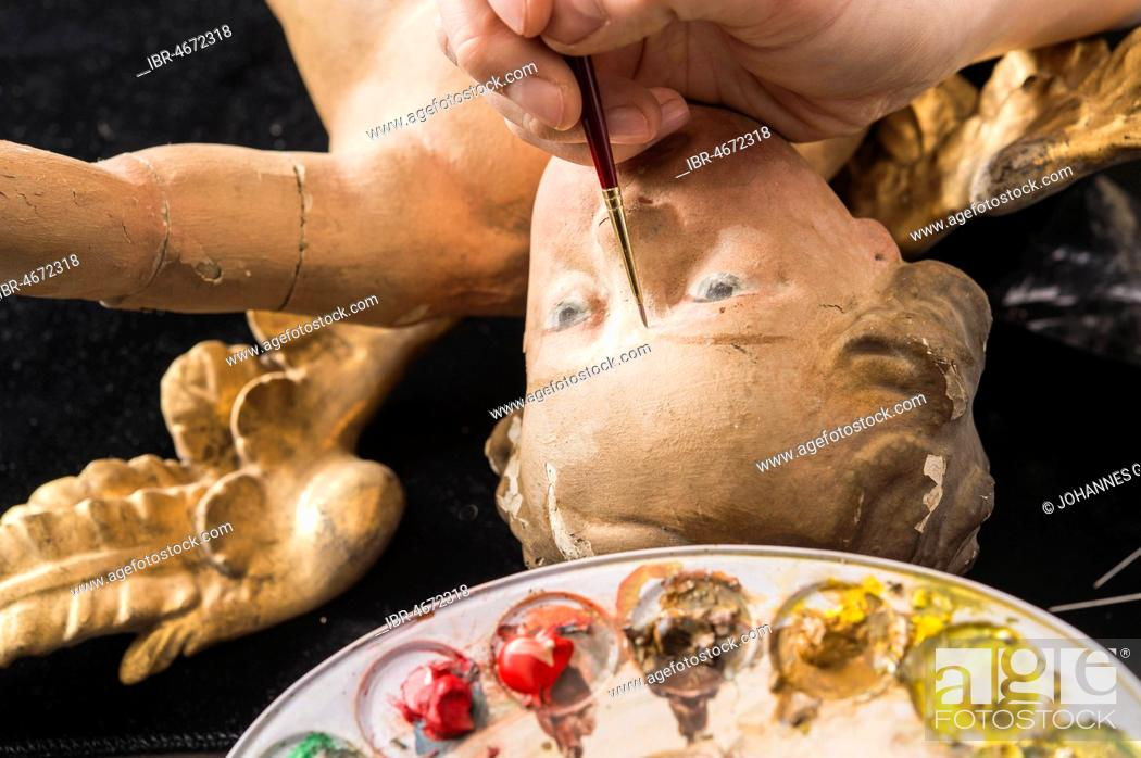 Stock Photo: Restoration studio, restorer, filling material is adapted to the angel's face with brush and paint, Munich, Bavaria, Germany.