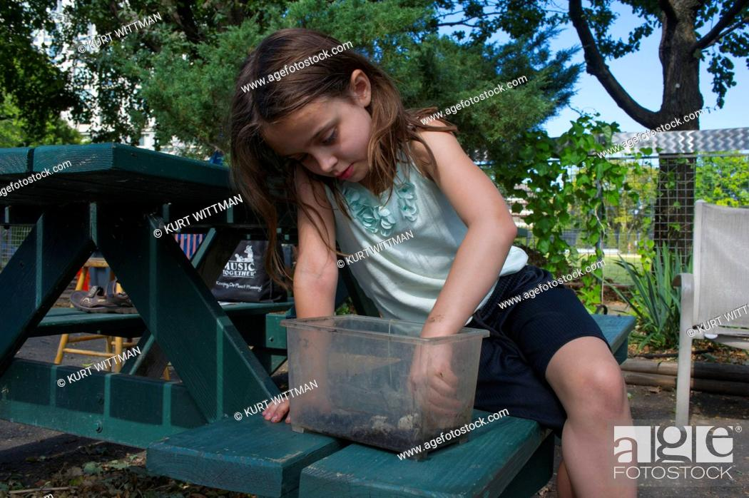 Stock Photo: Girl Playing with Bugs in Garden.