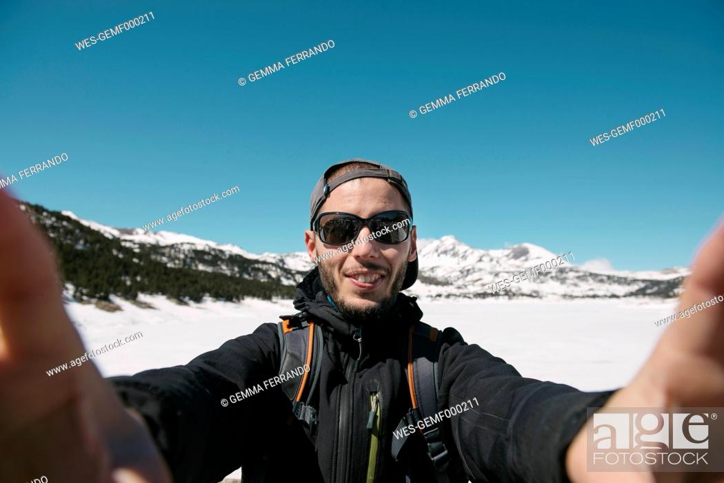 Stock Photo: Spain, Catalonia, man taking a selfie in the mountains with frozen Lac des Bouillouses in the background.