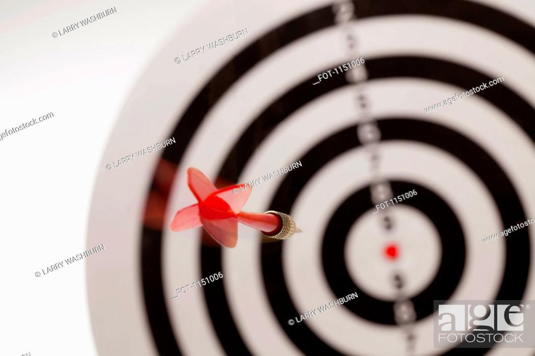 Stock Photo: Rear view of a dart flying towards the bull's eye of a target.