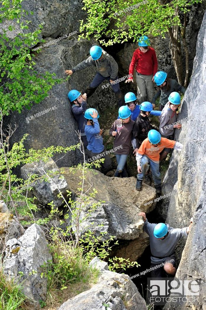 Stock Photo: School children during survival day clambering on eroded rocks of ravine in the nature reserve Fondry des Chiens, a sinkhole near Nismes at Viroinval in the.