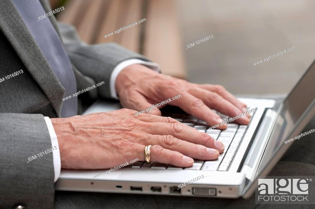 Stock Photo: Senior businessman, Close-up of human hands using laptop.