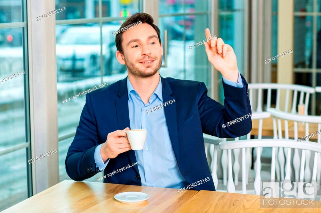 Stock Photo: Time to leave. Handsome young man is holding coffee mug and pointing his finger up to call a waiter.