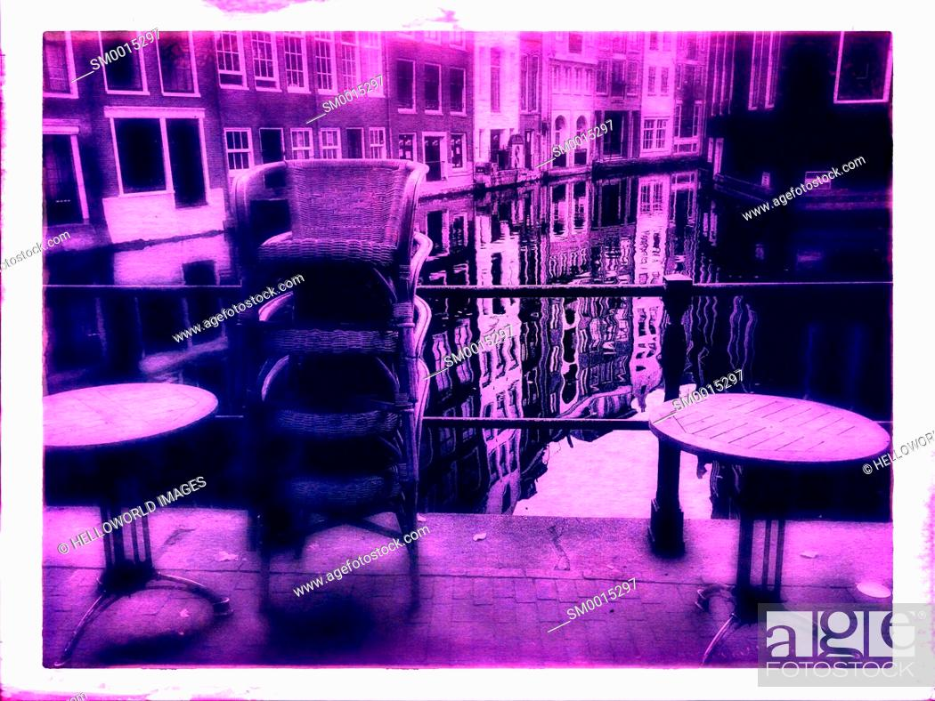Stock Photo: Pink tint of closed cafe terrace next to canal, Amsterdam, Netherlands.