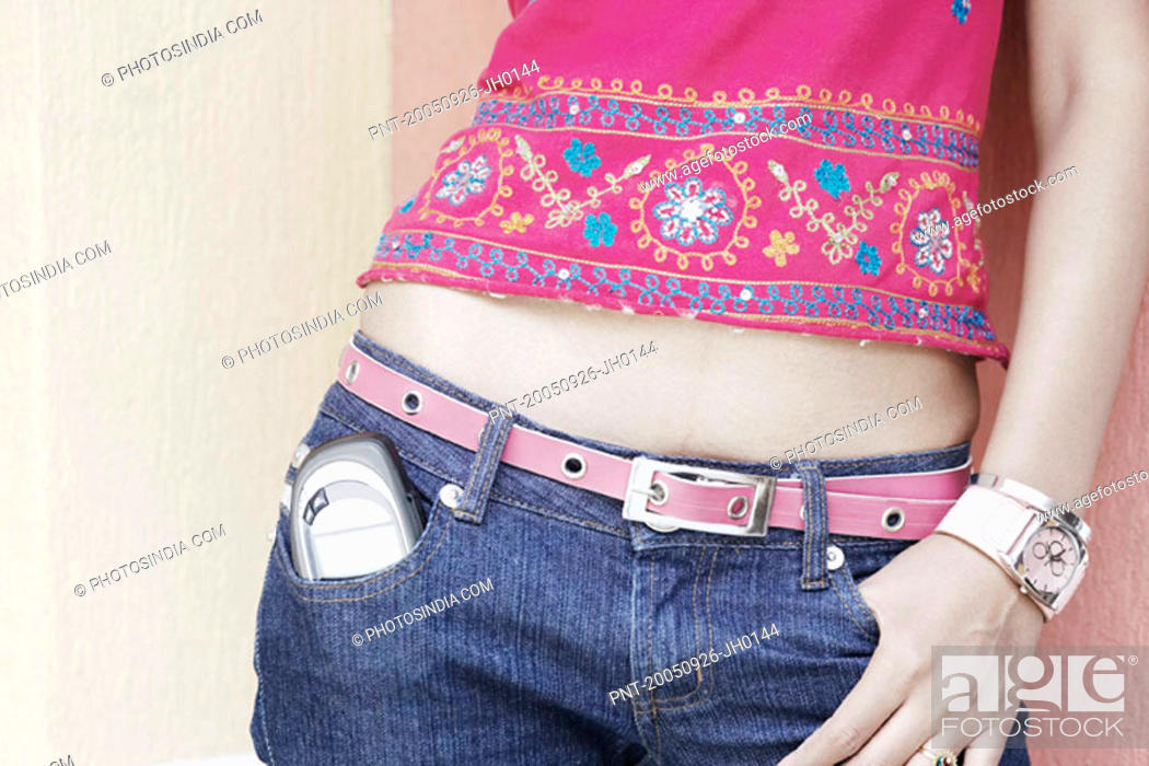 Stock Photo: Mid section view of a woman with a mobile phone in her pocket.