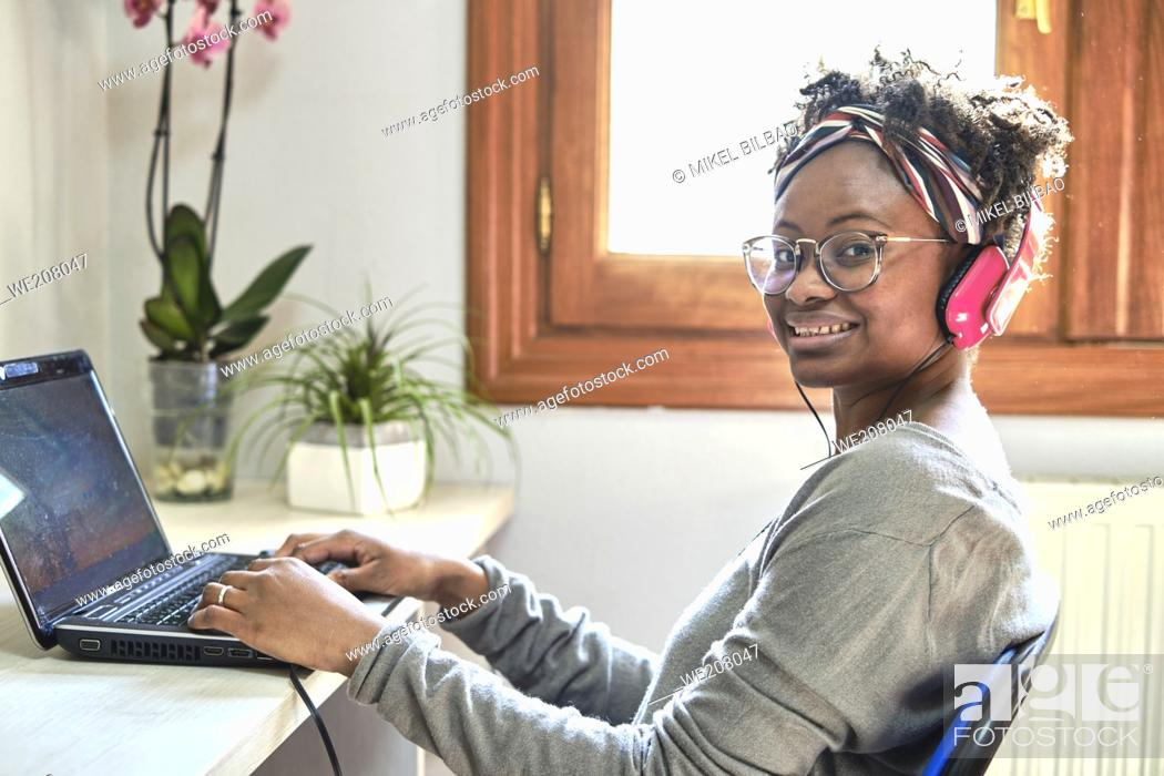 Photo de stock: Young black woman with afro hairstyle and a computer and listening music with headphones indoor in a house. Lifestyle concept.