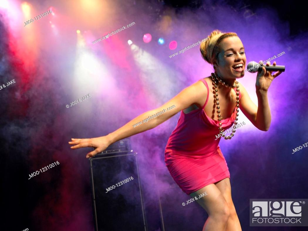 Stock Photo: Young Woman Singing on stage in Concert low angle view.