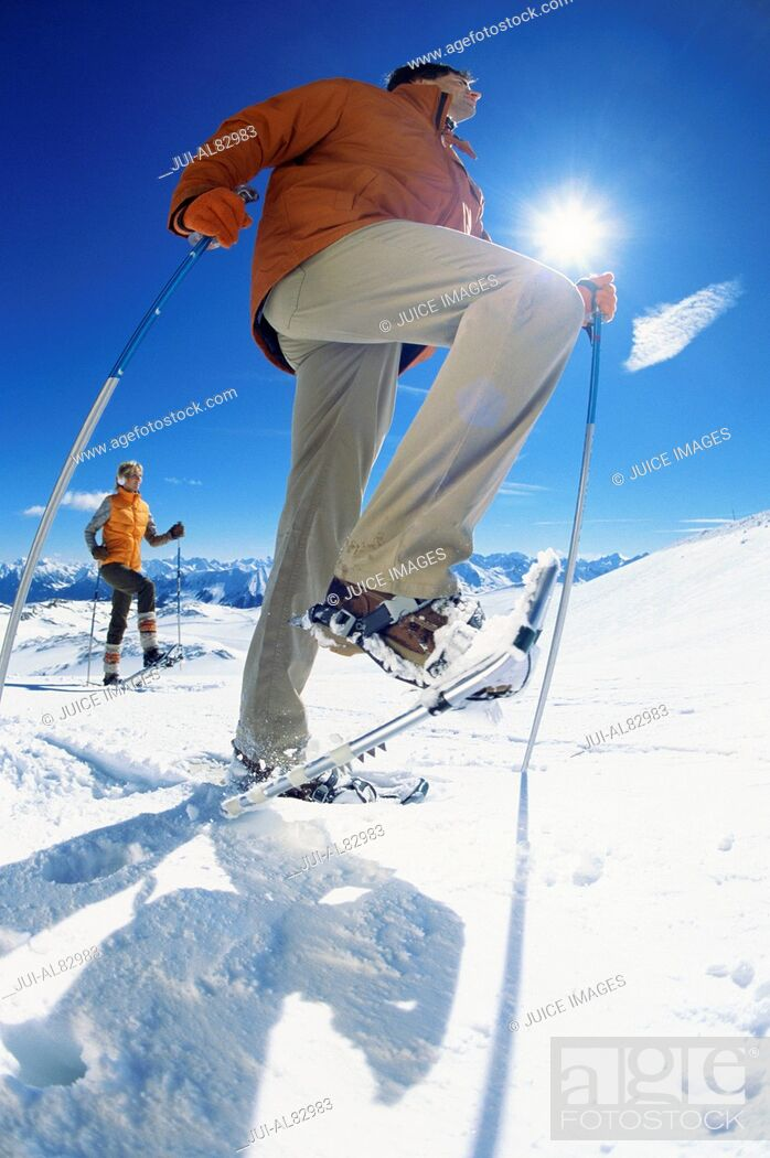 Imagen: Low angle view of couple snowshoeing with ski poles.