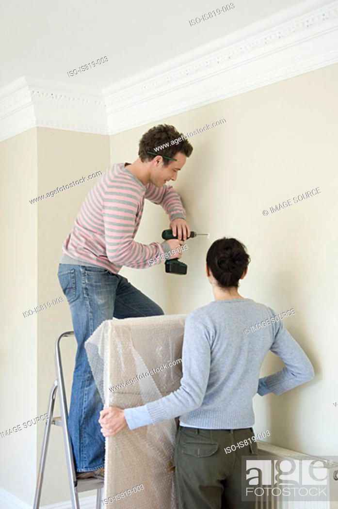 Stock Photo: Couple drilling wall.