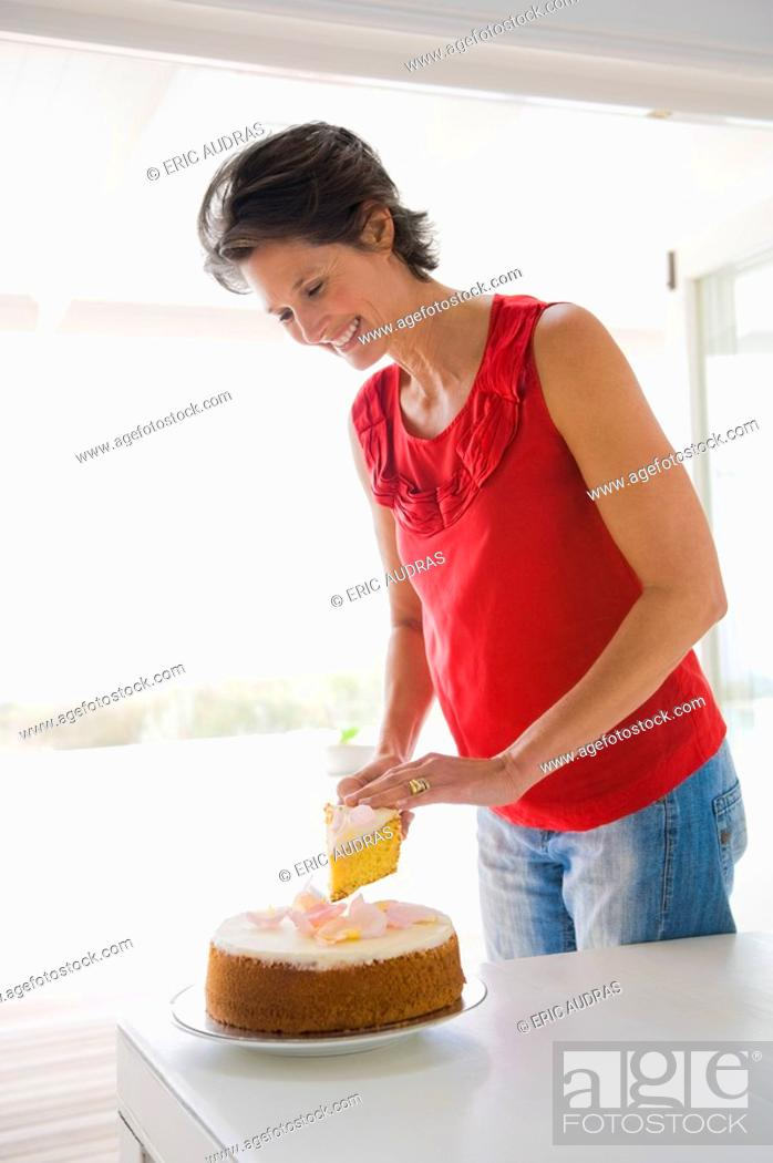 Stock Photo: Woman cutting a cake and smiling.