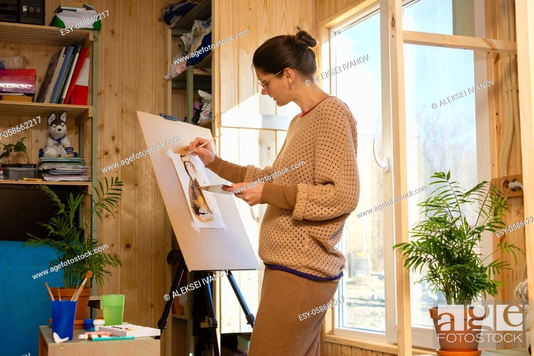 Stock Photo: Girl artist draws on an easel at home, molubert stands at the window.