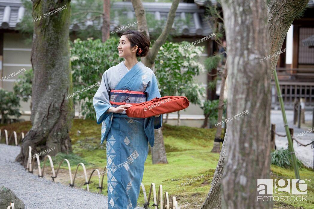 Stock Photo: Young Japanese woman in kimono walking into Japanese garden.