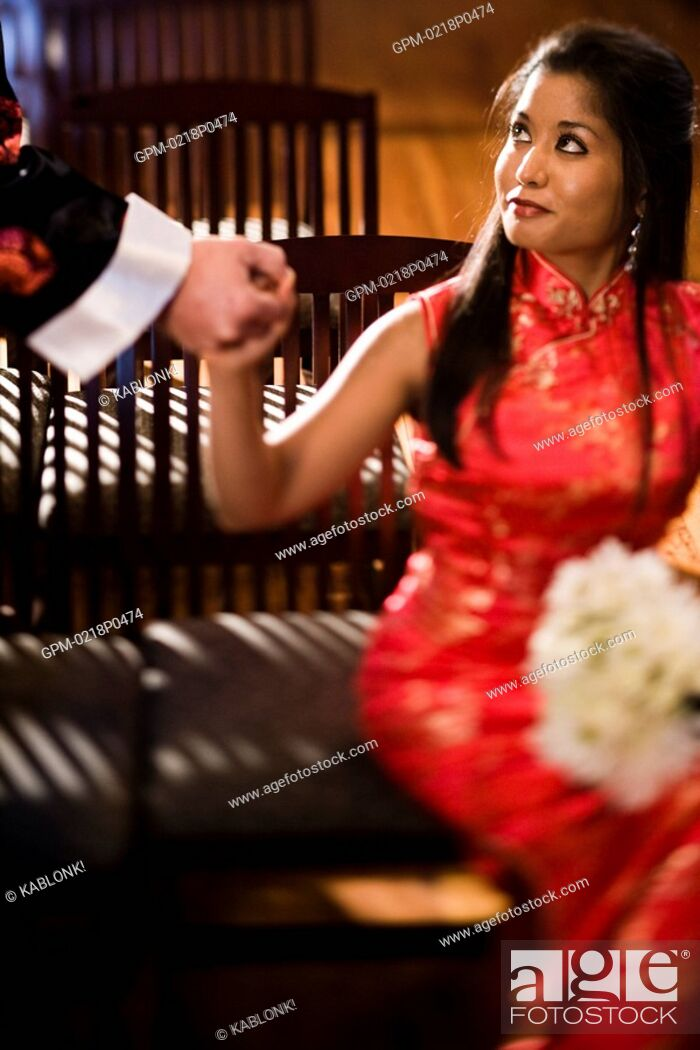 Imagen: Young Asian woman in traditional dress holding outstretched hand of man, selective focus.