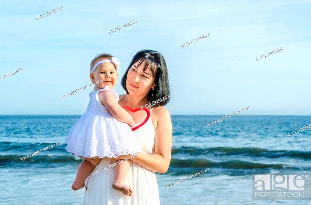 Stock Photo: Mother and her baby girl on the sandy beach near ocean in sunny day/Mothers day concept.