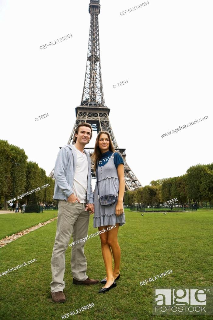 Stock Photo: Young couple standing in park with Eiffel tower in background, Paris, France.