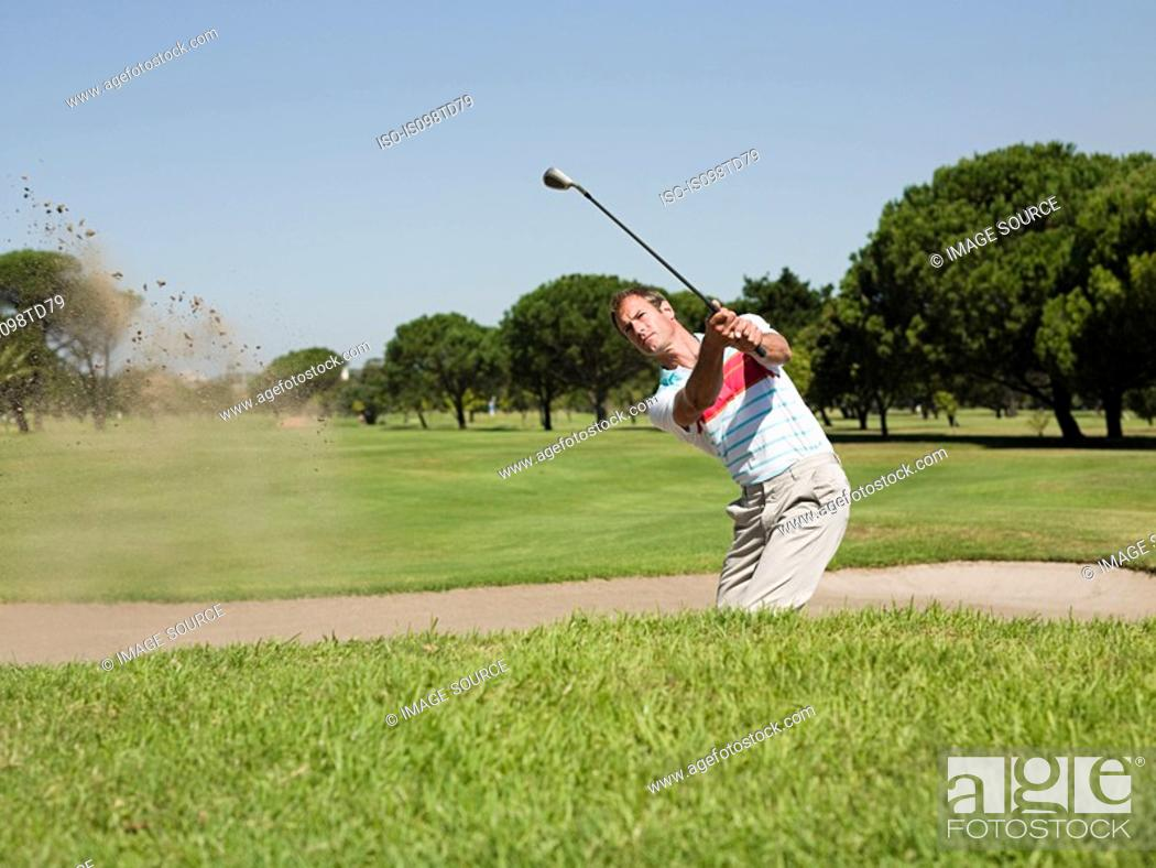 Stock Photo: Man playing golf, stuck in bunker.