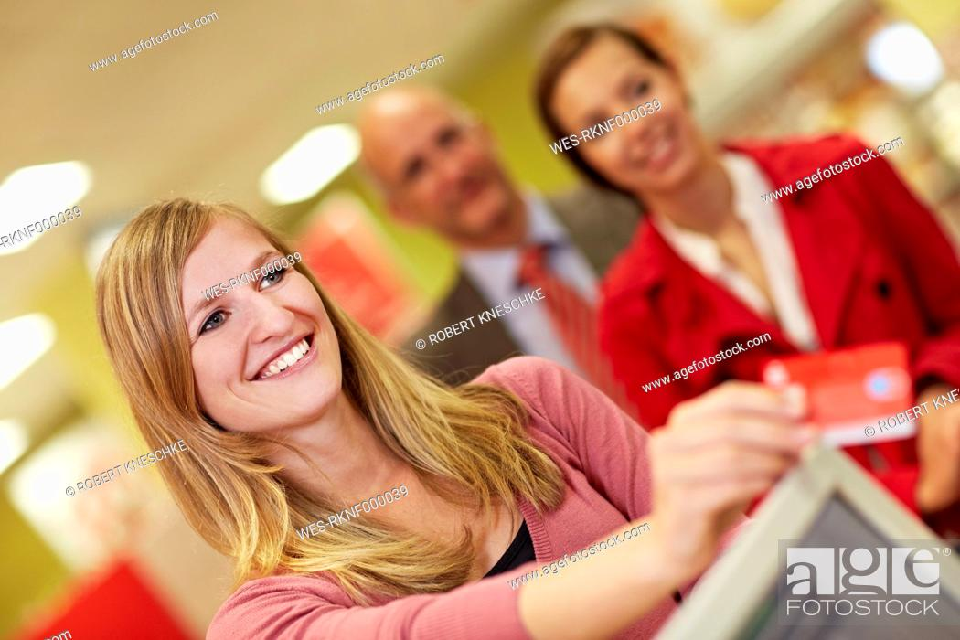Stock Photo: Germany, Cologne, Woman using credit card in supermarket.