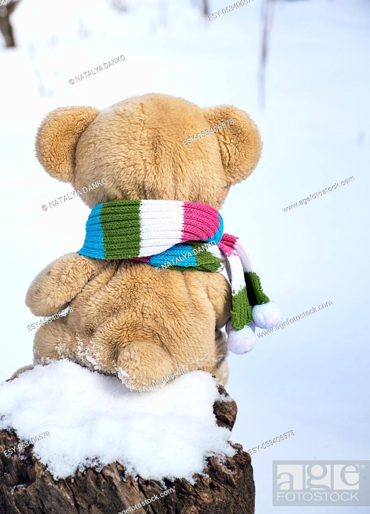 Stock Photo: teddy bear in a scarf sits backwards on a stump in the middle of white snow on a winter day.