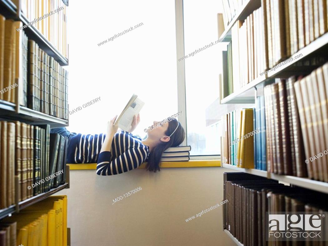 Stock Photo: Student lying down on windowsill in library reading.