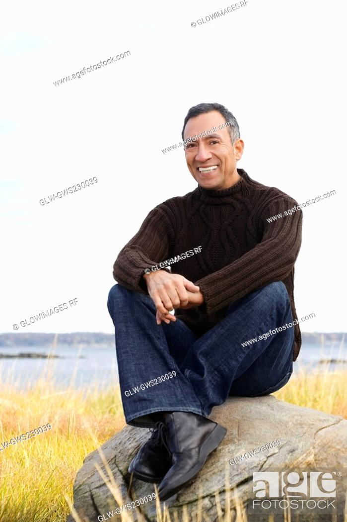 Stock Photo: Portrait of a mature man sitting on a rock and smiling.