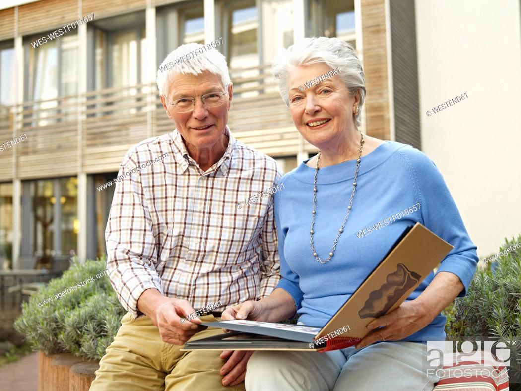 Stock Photo: Germany, Cologne, Senior couple with photo album in front of nursing home, portrait.
