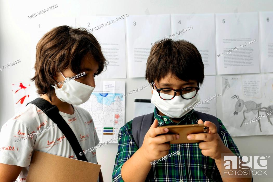 Stock Photo: Boy wearing mask looking at friend using smart phone while standing against wall in school.