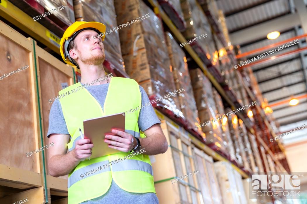 Stock Photo: Portrait white caucasian warehouse worker stand with digital tablet for inventory checking in large warehouse distribution center.