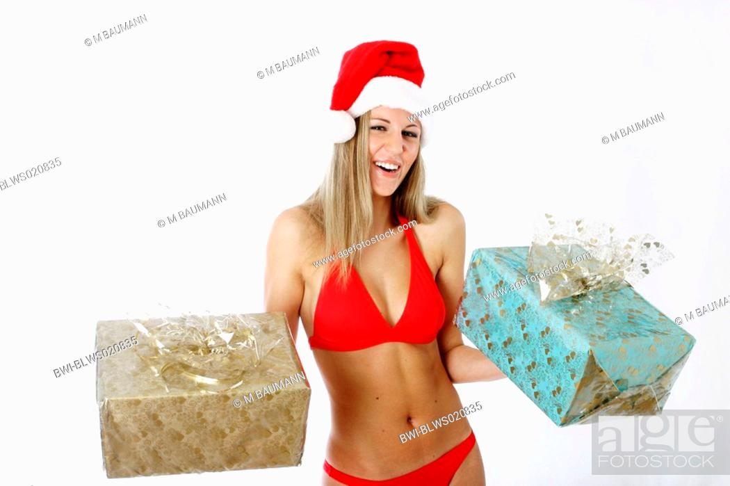 78f536c333 Stock Photo - blond woman with Christmas gifts and Santa Claus cap