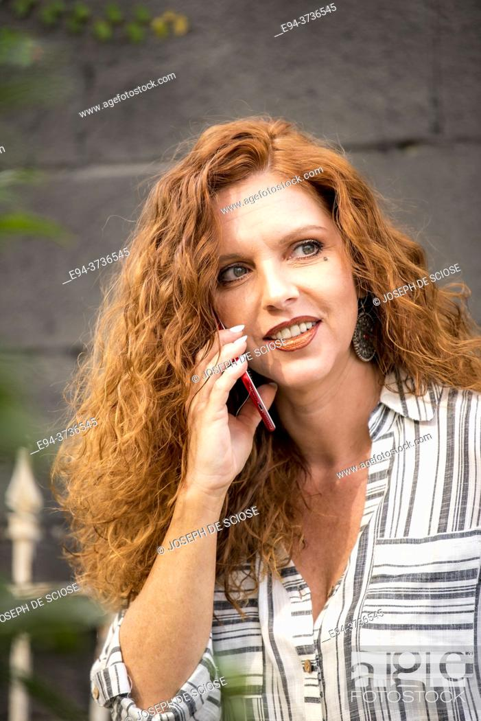 Imagen: A beautiful 41 year old redheaded woman speaking on a cell phone.