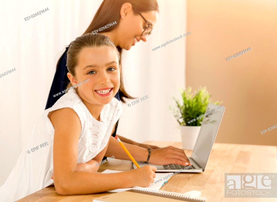 Stock Photo: Mother helping her little daughter how to use a computer.