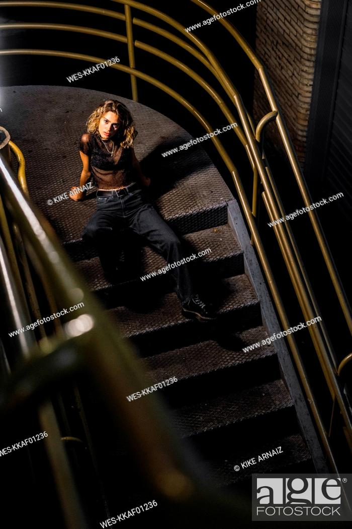 Stock Photo: Stylish young woman sitting on stairs at night.