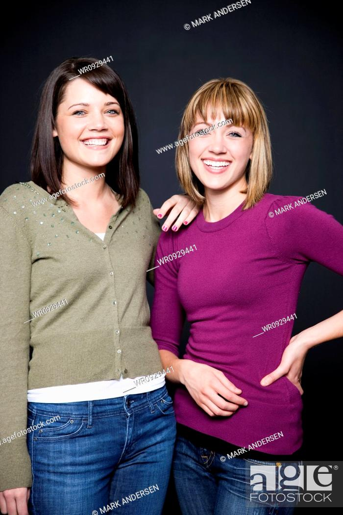 Stock Photo: Studio portrait of two young women, smiling.