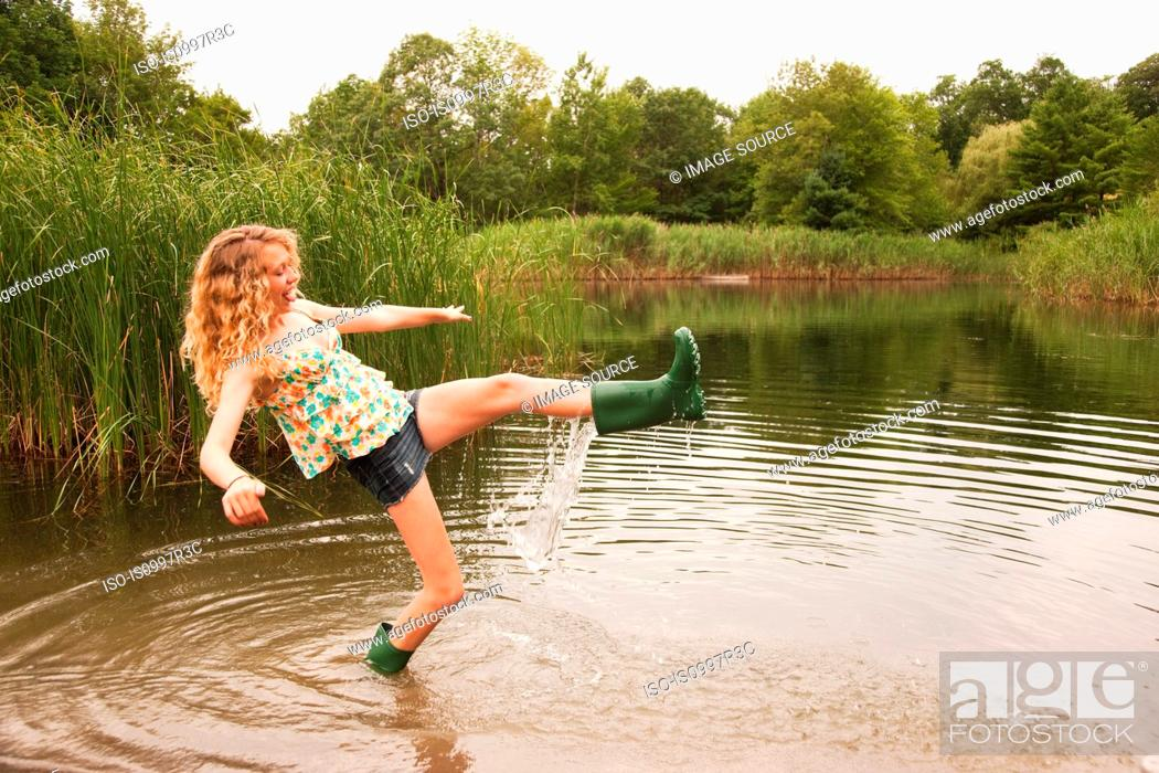 Stock Photo: Teenage girl wading into the middle of a lake with over-flowing wellies.