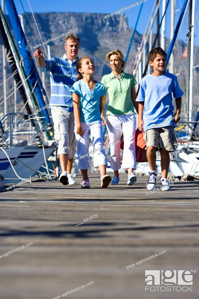 Stock Photo: Family walking along harbour jetty, father pointing, smiling, front view.