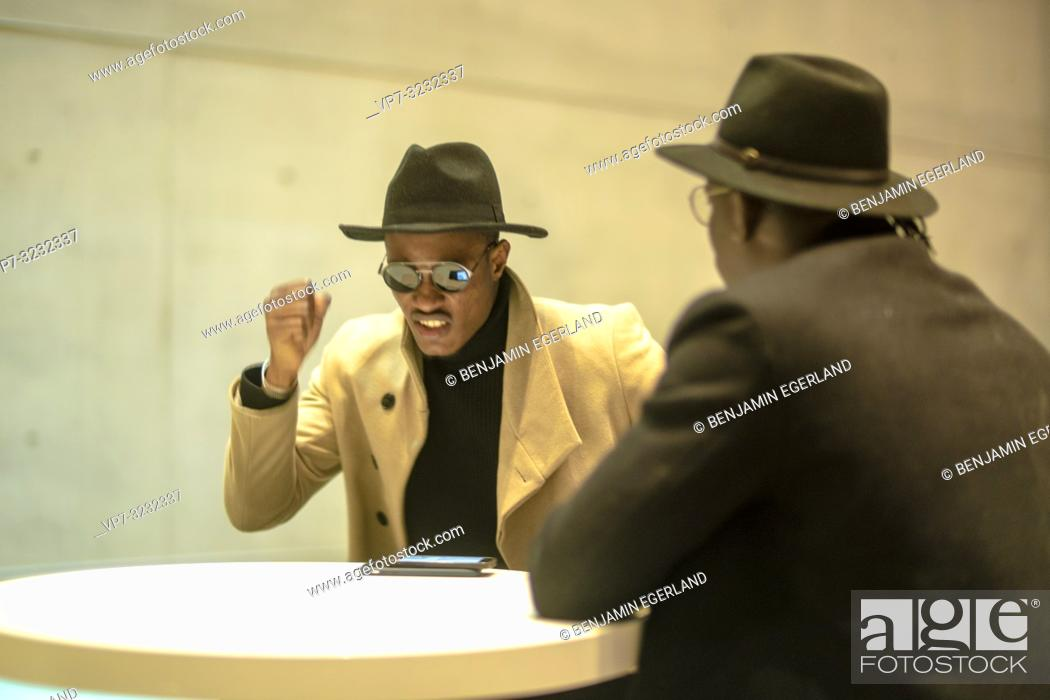 Stock Photo: furious man hitting hand at table during conversation with companion, freak out, indoors, in Munich, Germany.