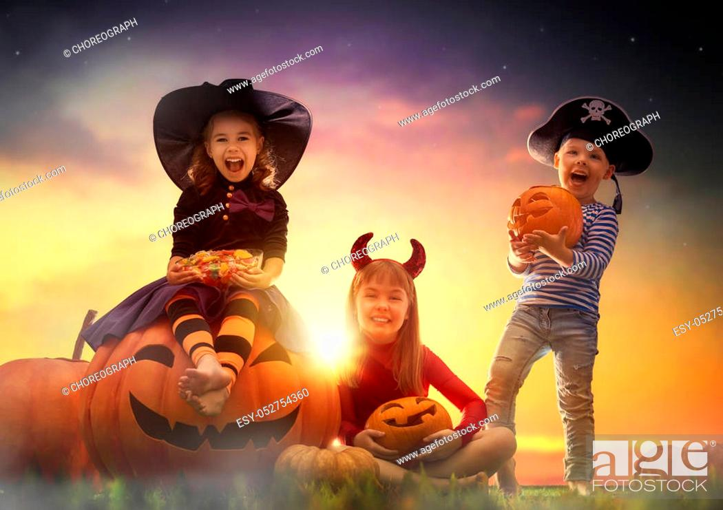 Imagen: Happy brother and two sisters on Halloween. Funny kids in carnival costumes outdoors. Cheerful children and pumpkins on sunset background.