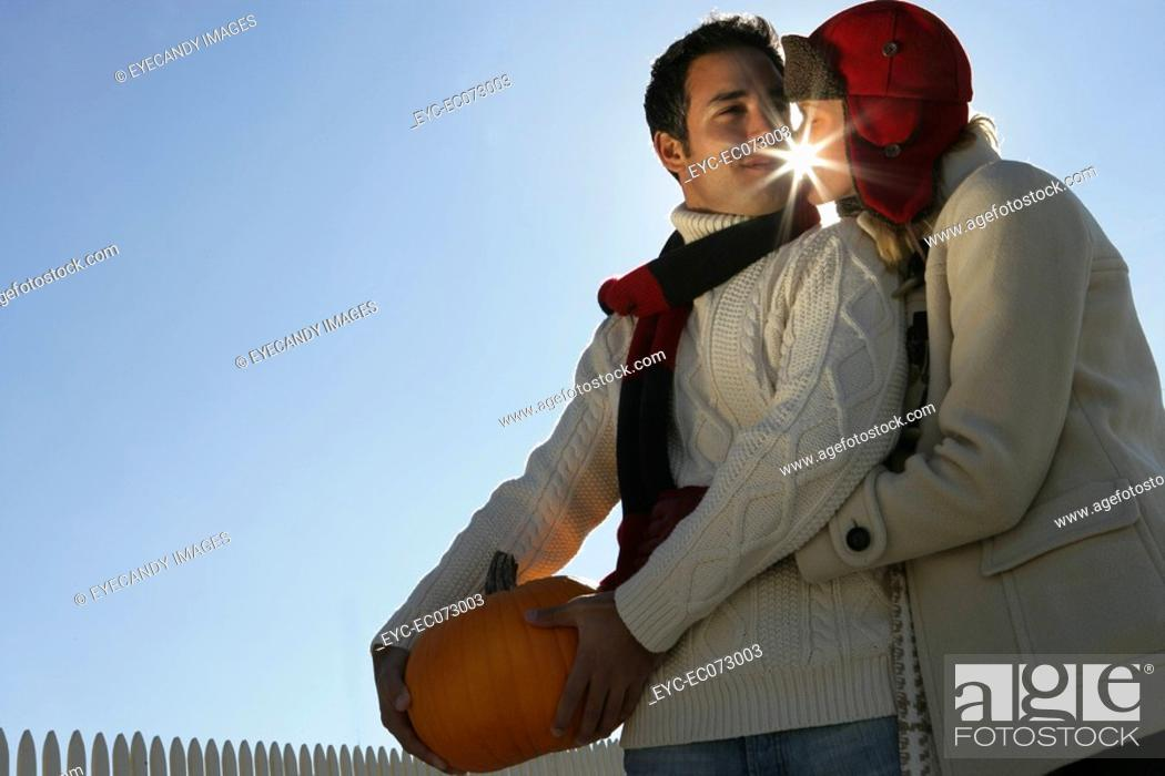 Stock Photo: Young affectionate couple with pumpkin.