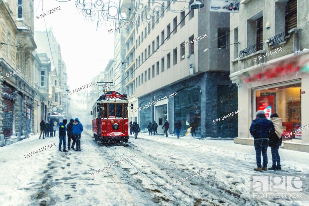 Photo de stock: Winter view of nostalgic red Tram and people in daily life while snowing at popular Istiklal Street of Beyoglu, Istanbul, Turkey. 07 January 2017.