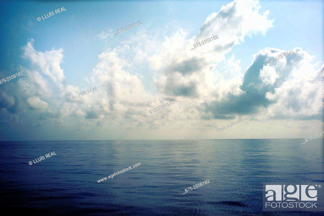 Stock Photo: Calm Mediterranean sea with clouds in the blue sky.