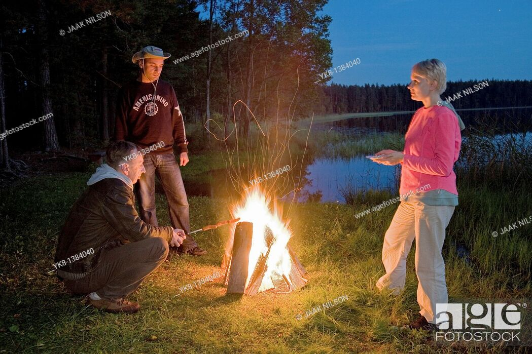 Stock Photo: Hikers Companion by Campfire near Water in Night.