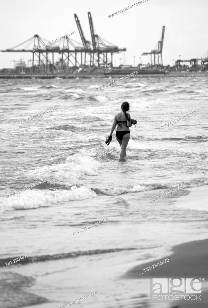 Stock Photo: woman strolling along the beach of Valencia.