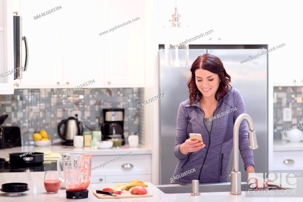 Stock Photo: Caucasian woman texting on cell phone in domestic kitchen.