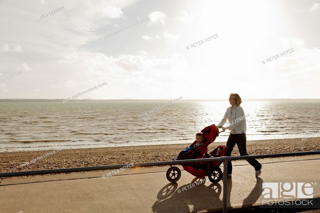 Stock Photo: Mother and children with pushchair walking on promenade with sea as background.