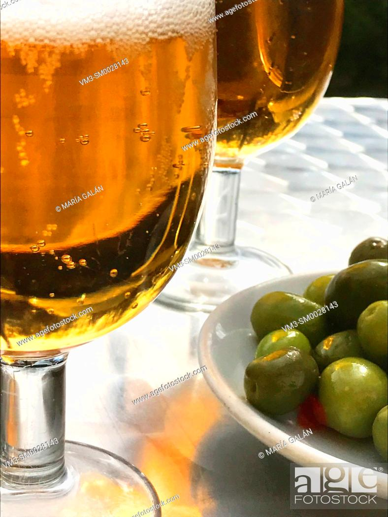 Stock Photo: Two glasses of beer with green olives. Close view.