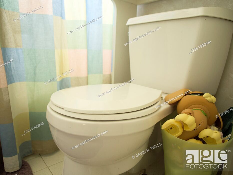 Stock Photo: Toys in basket next to toilet inside a foreclosed home in Talahassee, Florida, United States.