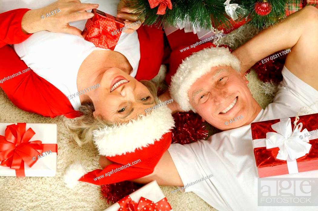 Stock Photo: Portrait of happy senior couple in Santa hats celibrating Christmas or New Year.