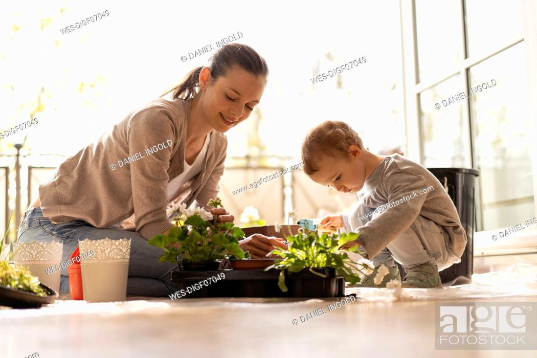 Imagen: Mother and daughter planting flowers together on balcony.