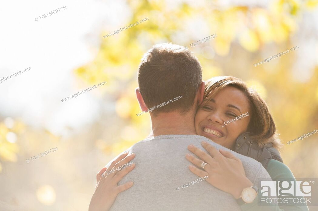Stock Photo: Enthusiastic couple hugging outdoors.