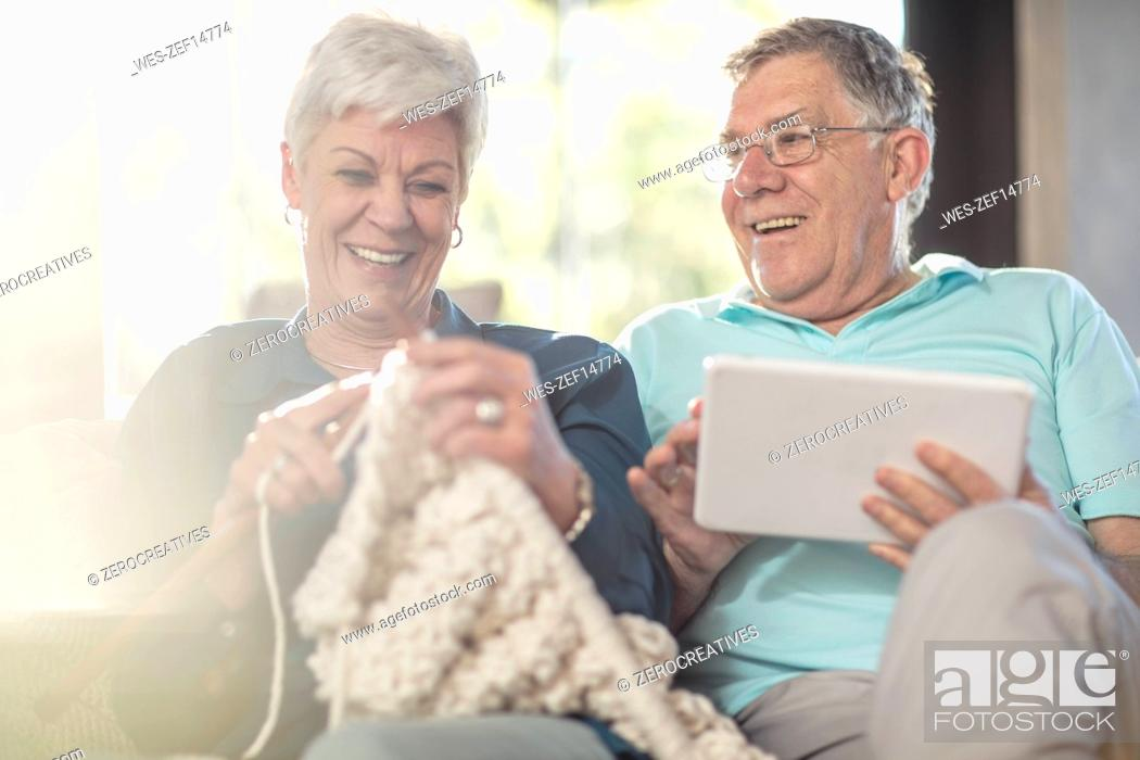 Stock Photo: Happy senior couple on couch at home knitting and using tablet.